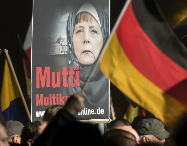 """A banner reading """"Mum multiculti"""" and depicting a manipulated image of German Chancellor Angela Merkel is carried by a ..."""