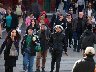 Pedestrians cross Flinders Street near Swanston Street in Melbourne's CBD