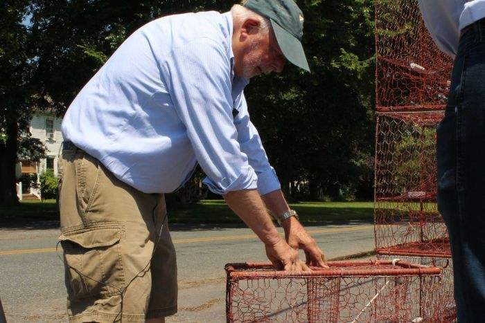 An older white man leans over a crab cage.