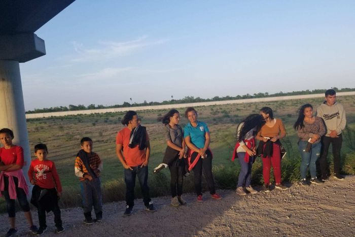 Women, men and children line up on the side of a dirt road