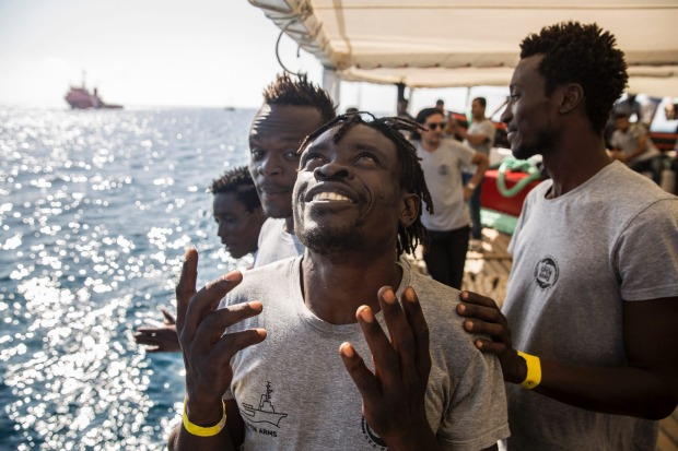Migrants aboard the Open Arms aid boat, of Proactiva Open Arms Spanish NGO, react as the ship approaches the port of ...