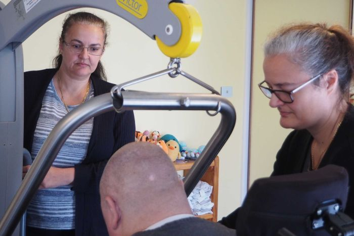 Two women provide help to a man with tetraplegia.